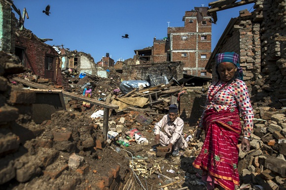 Local residents clear rubble from the ruins of their home after the April 25 earthquake in Sankhu, on the outskirts of Kathmandu