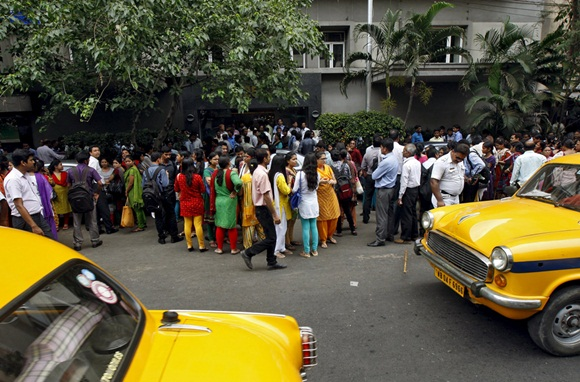 People stand outside a office building after vacating it following an earthquake in Kolkata
