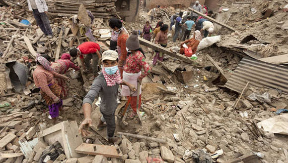 Varios nepalíes caminan entre las ruinas de los edificios. Foto: EFE.