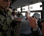 Un soldado israelí pide la documentación a un palestino en un control | REUTERS