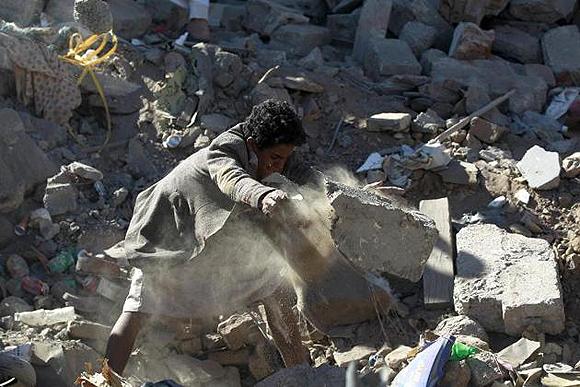 Un hombre aparta cascotes en busca de posibles supervivientes entre los escombros de un edificio destruido por los ataques aéreos nocturnos comandados por Arabia Saudí. Foto: AFP
