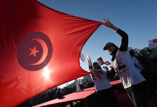 Una persona ondea la bandera tunecina en una manifestación en el 2014. Foto: Fethi Belaid/AFP
