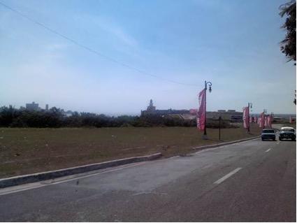 """Banderolas Rosa de la """"Zona Franca"""" que agrupa a expositores de la plástica contemporánea cubana expuesta en el complejo Morro Cabaña.  Al fondo el Morro y la entrada de la Bahía. Foto del autor."""
