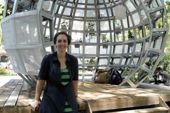 La artista neoyorkina Mary Mattingly posa junto a su obra titulada Pull, Propuesta de un lugar en el medio: sin puerta y sin paredes. Pieza que  imagina ciudades hechas de partes destinadas a ser móviles y maleables. Es una isla, un ecosistema y un organismo en formación. Expuesta en el Parque Central, como parte de la XII Bienal de La Habana. Foto: Roberto Morejón/ AIN.