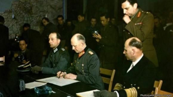 """A las 2:41 de la madrugada del 7 de mayo de 1945, el general Alfred Jodl, jefe del Estado Mayor de la Wehrmacht (Ejército Nazi), firmó el acta de rendición incondicional, que decía: """"Todas las fuerzas bajo el mando alemán cesarán las operaciones activas a las 23:01 horas, hora de Europa Central, del 8 de mayo de 1945"""". El documento ruso respetó la misma fecha y hora (23:01 del 8 de mayo, hora de Berlín), pero como en Moscú ya era 9 de mayo, este es el día en el que los rusos conmemoran la Victoria."""