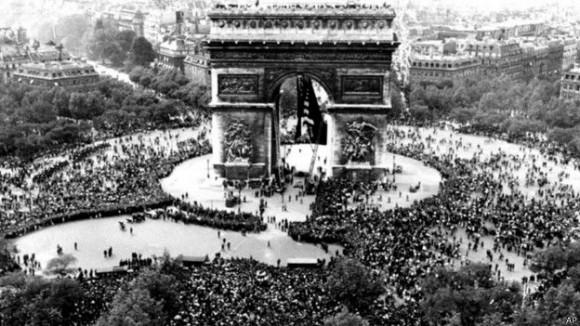 Una feliz multitud se reunió en el Arco del Triunfo en París cuando se anunció la rendición de Alemania ante los Aliados.