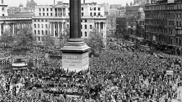 """Enormes multitudes de reunieron en Londres. A las 3:00 el primer ministro Winston Churchill dio un discruso por radio. En la Plaza de Trafalgar su voz se escuchó en los altavoces y, en voz, de un testigo, """"hubo un extraordinario silencio sobre la multitud reunida""""."""