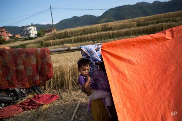 Una mujer nepalí lleva a un niño y se encuentra al lado de una tienda de campaña en Nalinchowk, cerca de Katmandú, Nepal, jueves, 14 de mayo de 2015. El 25 de abril, un terremoto de magnitud 7,8 mató a miles de personas, hirió a decenas de miles más y dejó a cientos de miles sin hogar. Entonces, justo cuando el país comenzaba a reconstruir, un terremoto de magnitud 7,3 azotó de nuevo. (Foto AP / Bernat Amangue)
