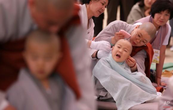 Un muchacho joven cuyo nombre es budista Chung Bin reacciona como un monje budista de Corea del Sur se afeita la cabeza durante un servicio para celebrar el cumpleaños de 2559a la próxima Buda el 25 de mayo en el templo Jogye en Seúl, Corea del Sur, Lunes, 11 de mayo de 2015. Él es uno de los nueve niños que entraron en el templo para tener una experiencia de la vida de los monjes durante dos semanas. (Foto AP / Lee Jin-man)