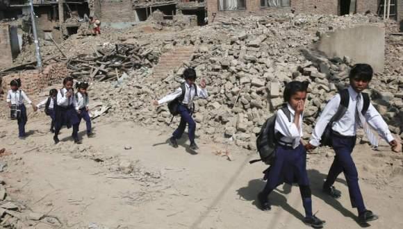 Un grupo de escolares pasa junto a una montaña de escombros en su primer día de la vuelta al colegio, cinco semanas después del terremoto en Nepal. Aún así, la inmensa mayoría de los niños y niñas afectados por el seísmo en ese país siguen sin poder ir a la escuela. (EFE)