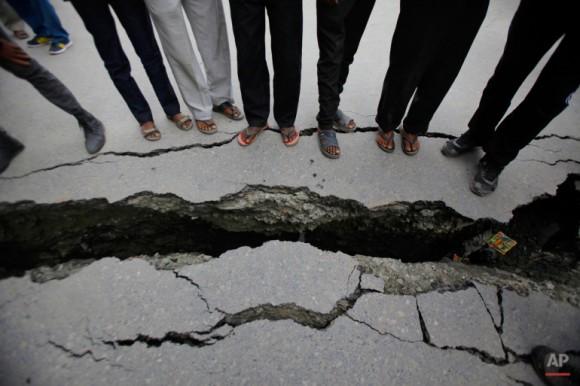 Nepaleses miran una carretera agrietada después de un terremoto en Katmandú, Nepal, el domingo 26 de abril de 2015. (Foto AP / Niranjan Shrestha)