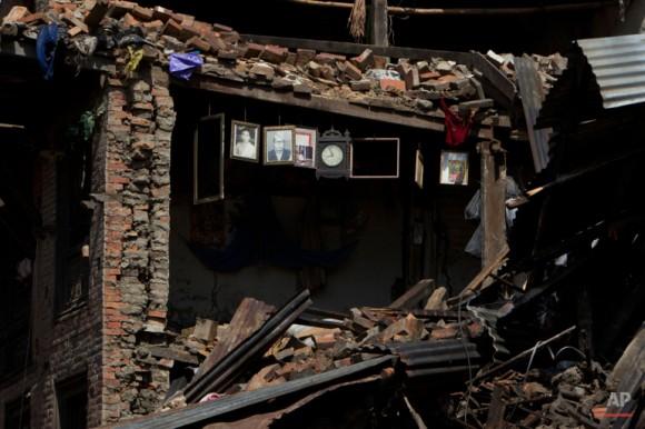 Retratos y un reloj de pared se ve colgando sobre los restos de una casa dañada en el terremoto del sábado en Bhaktapur, en las afueras de Katmandú, Nepal, Lunes, 27 de abril de 2015. Un terremoto de fuerte magnitud sacudió la capital nepalíes y el valle de Katmandú densamente poblada en Sábado devastando la región y dejando a decenas de miles conmocionado y durmiendo en las calles. (AP Photo / Niranjan Shrestha)