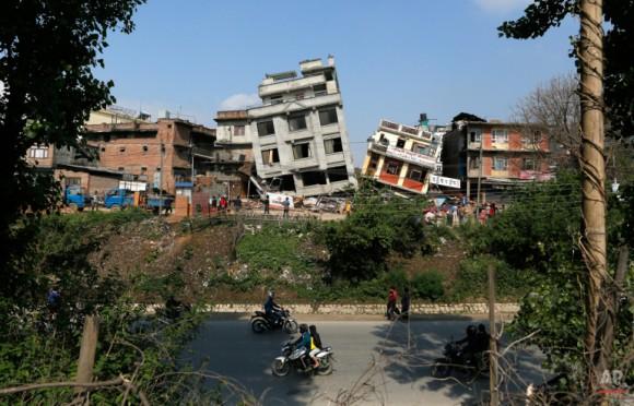 Edificios dañados magras a sus lados en Katmandú, Nepal, Lunes, 27 de Abril de 2015. Un fuerte terremoto de magnitud 7,8 sacudieron la capital de Nepal y el Valle de Katmandú densamente poblada del sábado, causando grandes daños con paredes derribados y se derrumbaron edificios. (AP Photo / Wally Santana)