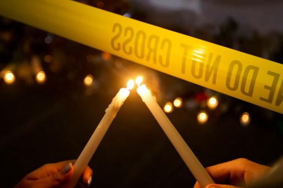 Olina Ortega, izquierda, y Austin Gibbs encienden velas en el memorial de la acera. Foto: David Goldman/ AP