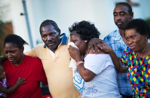 Gary y Aurelia Washington, centro izquierda y derecha, hijo y nieta de Ethel Lance, quien murió en el tiroteo del miércoles, dejan un memorial en la acera delante de la Iglesia Emanuel. Foto: David Goldman/ AP