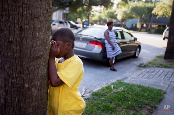 ArQuadious Holmes, de 9 años, sobrino nieto de Susie Jackson, quien murió en el tiroteo del miércoles, juega a las escondidas mientras la sobrina de Jackson, Sherry Alcaparras, se apoya en un coche durante una reunión de la familia fuera de la casa de Jackson. Foto: David Goldman/ AP