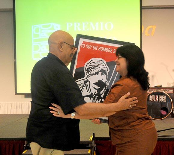 El presidente de la Upec, Antonio Moltó, hizo entrega de un reconocimiento a la Asociación Cubana de Comunicadores Sociales. Foto: Ismael Batista / Granma