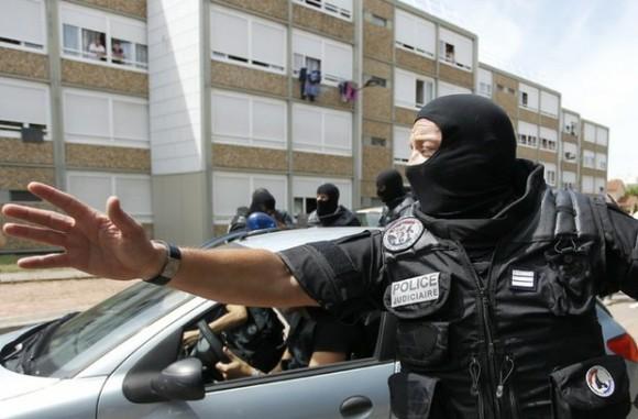 Un agente de la policía especial de Francia, vigila un edificio residencial en Saint-Priest, cerca de Lyon, donde se reportó este viernes un atentado terrorista que dejó un decapitado y varios heridos. Foto: Reuters