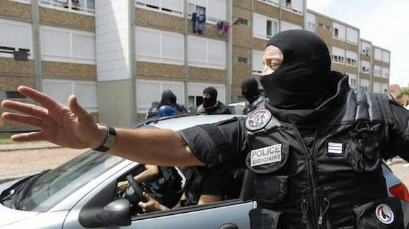 Un agente de la policía especial de Francia, vigila un edificio residencial en Saint-Priest, cerca de Lyon, donde se reportó este viernes un atentado terrorista que dejó un decapitado y varios heridos