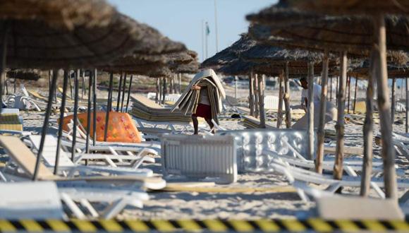 Un trabajador del hotel Marhaba imperial recoge las colchonetas de las tumbonas de la playa de Susa. Foto: EFE
