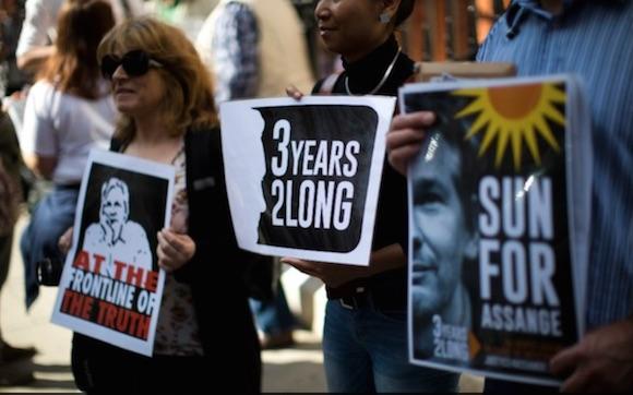 Personas se manifiestan en la embajada ecuatoriana donde se encuentra Julian Assange. En una de las pancartas se lee: Sol para Assange. Foto: AP