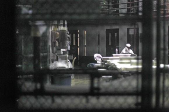 Un prisionero no identificado lee un periódico en un pabellón comunitario en el Camp VI, una prisión utiliza para los detenidos de las casas de Estados Unidos en Guantánamo Base Naval, 05 de marzo 2013. Bob Strong