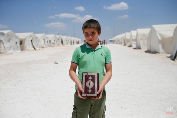 Un niño refugiado sirio posa sosteniendo una copia del Corán, el libro sagrado del Islam. Foto: Emrah Gurel/ AP