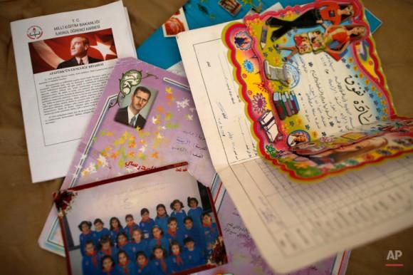 Una foto muestra informes de la escuela de un niño refugiado sirio, algunos de una escuela en Siria, cuando estudiaba allí, uno con una imagen del presidente sirio Bashar Assad, centro, y el actual, arriba a la izquierda, con una imagen del fundador de la República turca Mustafa Kemal Ataturk, de la escuela en un campamento de refugiados en Suruc, en la frontera entre Turquía y Siria. Foto: Emrah Gurel/ AP