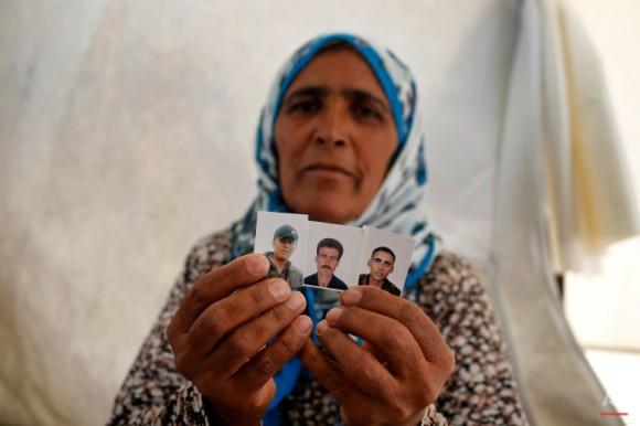 La refugiada kurdo-siria Sidika Hemed, de 52 años, sostiene fotos de su hermano Abdullah Muhammad, al centro y de sus hijos Fevaz Kahraman 24, izquierda, y Celal Kahraman, derecha, todos muertos por militantes del grupo Estado Islámico. Foto: Emrah Gurel/ AP
