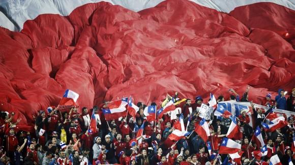 Fanáticos de Chile despliegan una bandera gigante sobre la tribuna durante el partido entre su equipo y Uruguay, por los cuartos de final de la Copa América, en Santiago. Chile ganó 1 a 0 y consiguió el pase a las semifinales. Foto: AP