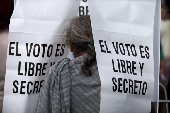 Un mujer medita su voto en Tixtla (Guerrero) donde se han registrado enfrentamientos y quema de urnas. Foto: AP.