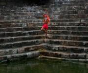 Un hombre santo Sadhu o hindú realiza yoga en las escaleras de Saubhagya Kund, un estanque sagrado, en el templo Kamakhya en Gauhati, India, el martes, 23 de junio de 2015. Cientos de sadhus, hombres santos hindúes o, han llegado para el cinco días del festival para realizar rituales en el templo durante el festival anual Ambubasi que comenzó el lunes. Foto: Anupam Nath/ AP.