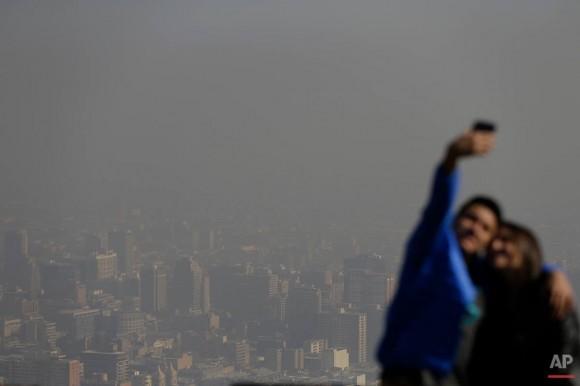 """Los turistas toman fotos de sí mismos desde el """"Cerro San Cristóbal"""", Chile. Foto: Jorge Saenz/ AP."""