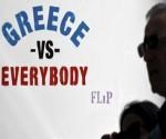 """Un hombre pasa junto a una pintada del artista callejero Flip, en Atenas, que dice """"Grecia contra todos"""". REUTERS/Alkis Konstantinidis."""