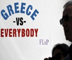 Un hombre pasa junto a una pintada del artista callejero Flip, en Atenas, que dice