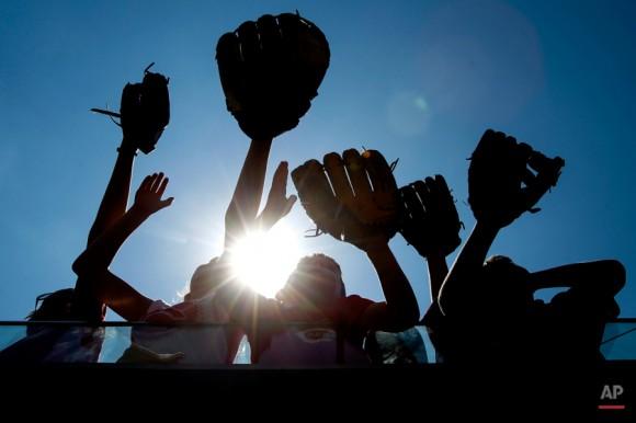 Los jóvenes seguidores abogan por pelotas de béisbol junto a la caseta de Rojos de Cincinnati durante un juego de béisbol contra los Filis de Filadelfia, Miércoles, 10 de junio 2015, en Cincinnati. Los Rojos ganaron 5-2. Foto: John Minchillo/ AP.