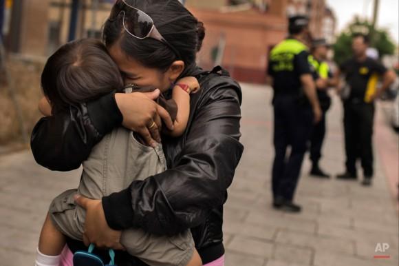 La policía y una charla de cerrajería como Karen Minan, 25 años, segundo izquierda, abraza a su hijo Aaron, uno y medio años de edad, después de que ella fue desalojada en Madrid, España, miércoles, 10 de junio de 2015. Karen Minan tiene 3 hijos y un recién nacido de menos de un mes de edad. Se desalojó como ella no podía permitirse el lujo de pagar el alquiler después de que su marido fue encarcelado por no pagar una multa de € 2,500. Andres Kudacki.