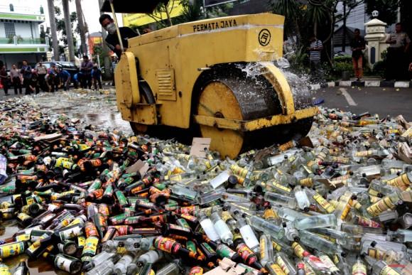 La policía utiliza una apisonadora para destruir botellas de alcohol ilegal confiscada en una campaña pre-Ramadán anti-alcohol, en Yakarta, Indonesia, miércoles, junio. 10, 2015. Cada Ramadán, el mes sagrado del calendario musulmán, el gobierno lleva a cabo redadas en tiendas de licores sin licencia y luego destruye el licor en una pantalla púbico. Indonesia es el país musulmán más poblado del mundo. Foto: Tatan Syuflana/ AP.