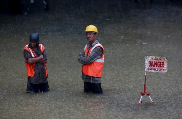 Al menos 13 personas han muerto y miles se han visto afectadas por lluvias torrenciales y deslizamientos de tierra asociados a la temporada de monzones en el estado indio de Meghalaya, en el noreste del país. En la imagen, trabajadores indios esperan bajo la lluvia en una carretera inundada en Bombay. Foto: Reuters.