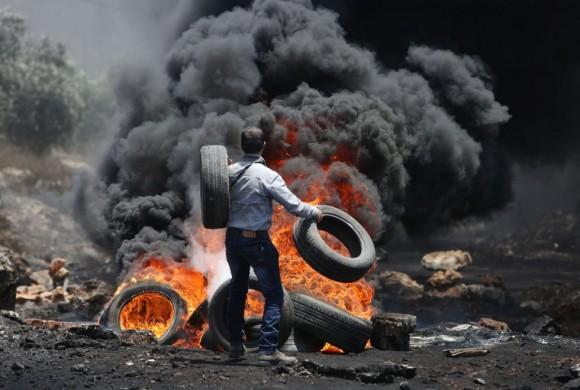 Un manifestante palestino lanza neumáticos en un hoguera durante una protesta cerca de la ciudad de Nablus (al norte de Cisjordania). Foto: AFP.