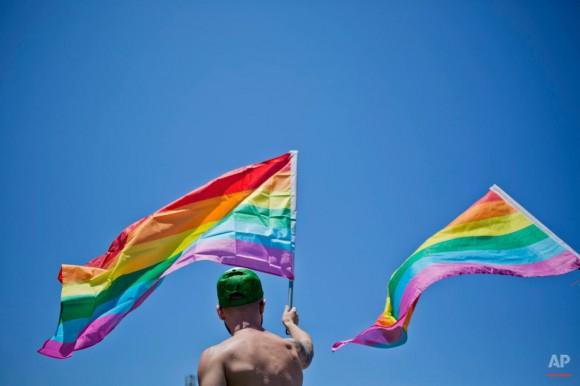hombre agita una bandera del arco iris en el Orgullo Gay desfile anual en Tel Aviv, Israel, Viernes, 12 de junio 2015. Ariel Schalit