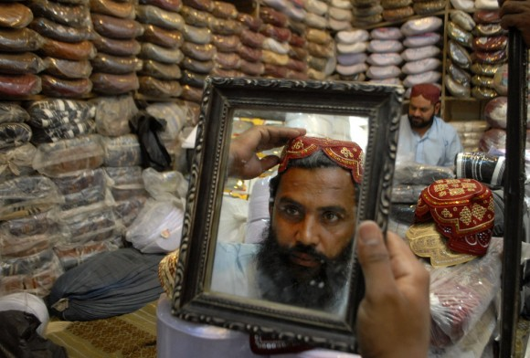 Un cliente se prueba una gorra tradicional para el Ramadán en una tienda de Peshawar (Pakistán). Foto: AP.