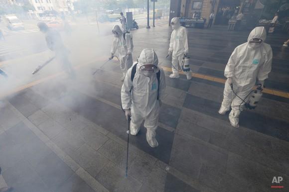 Los trabajadores que usan equipo de protección aerosol solución antiséptica como medida de precaución contra la propagación del MERS, Síndrome Respiratorio Oriente Medio, el virus fuera de la estación de metro de Wangsimni en Seúl, Corea del Sur, Jueves, 11 de junio 2015.  Ahn Young-joon