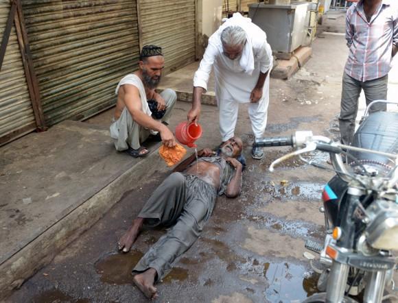 Varios vecinos de Karachi, corazón económico de Pakistán, ayudan a hidratarse a otro ciudadano. Solo en el hospital de Jinnah de esta ciudad, capital de la provincia de Sindh, han muerto en cuatro días 415 personas por la fuerte ola de calor. Foto: AFP.