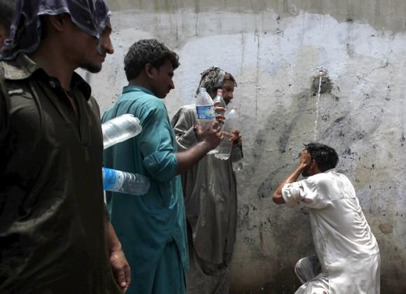 Un hombre trata de hidratarse en un grifo público en Karachi, en el sur de Pakistán, mientras otros aguardan para llenar sus botellas. El Gobierno ha levantado campamentos hospitalarios improvisados en las calles de la ciudad donde han muerto más de 400 personas en cuatro días. El balance en toda la provincia de Sindh es de casi 700 víctimas mortales. Foto: Reuters.