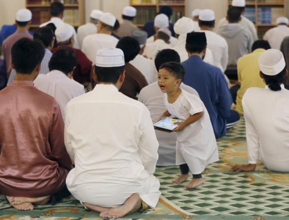un niño habla a su padre durante las oraciones tarawih, antes de Ramadán, en Kuala Lumpur, Malasia. Foto: Reuters.