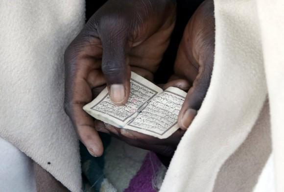 Detalle del Corán que está leyendo un inmigrante durante la oración a la salida del sol en el malecón del cruce fronterizo de San Ludovic, entre Italia y Francia. Foto: EFE.