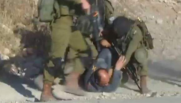soldados israelíes golpean a palestino