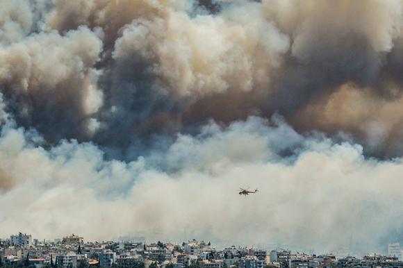 Labores de extinción del incendio que se ha producido en el monte Imitós de Atenas y que ha obligado a evacuar cinco pueblos y dos campamentos de verano. Foto: AFP