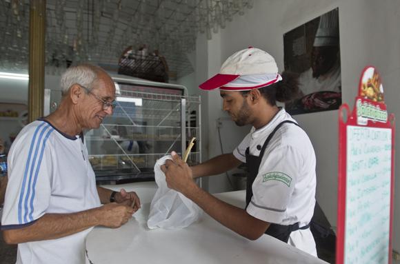 Dayron Pedroso atiende a un cliente que viene a la panadería por primera vez.  Foto: Ladyrene Pérez/ Cubadebate.